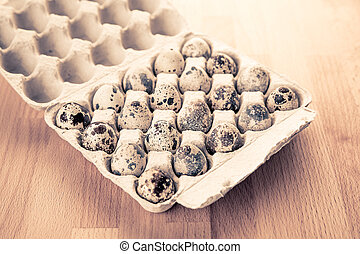 Box with quail eggs on the table