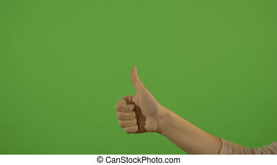 Female hand, gesture thumb up, on a green background....