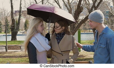 Meeting friends in the park. Two blonde girls and a brunette stand under an umbrella when it rains. A young man approaches them. They cheerfully say hello and talk.
