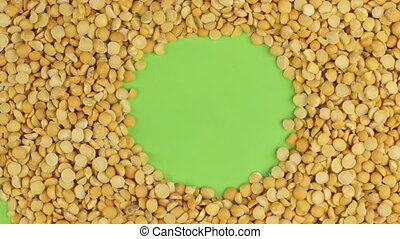Rotation of the peas grains lying on a green screen, chroma key.