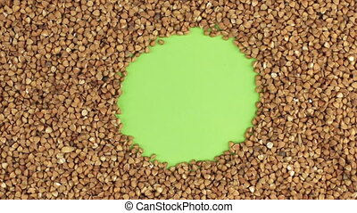 Rotation of the buckwheat grains lying on a green screen, chroma key.