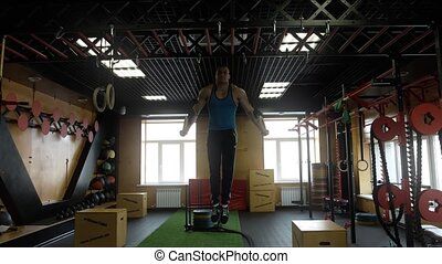 An athlete doing exercises on the rings in the hall of crossfit