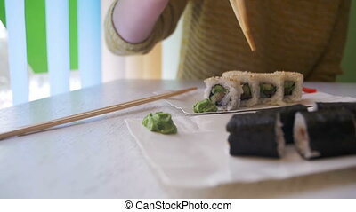 Girl with Chopsticks Taking Sushi Roll with Nori from a Plate in a Japanese Restaurant. Slow Motion