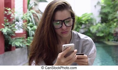 Woman in glasses use online banking on smartphone with...