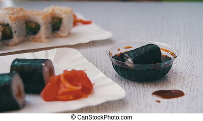 Chopsticks Taking Sushi Roll with Nori in Soy Sauce in a Japanese Restaurant. Slow Motion