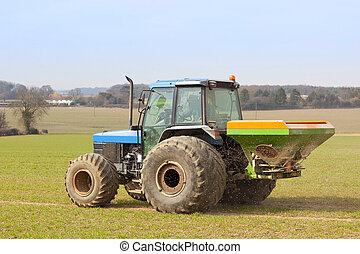spreading fertilizer - a tractor spreading fertilizer in...