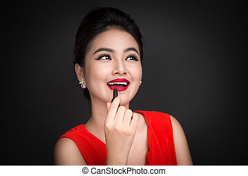Professional Make-up. Attractive asian model applying red...