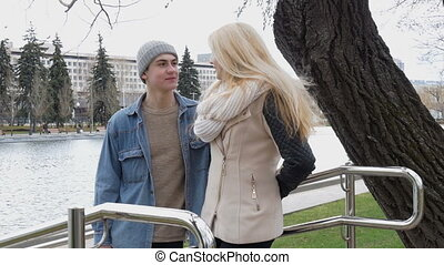 Young beautiful couple talking on a date, standing in a park in a pond. Sexy blonde girl.