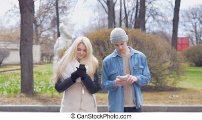 Two young people, a beautiful blonde and her friend, are walking down the street and using mobile phones. Write messages in the messenger.