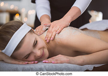 Young smiling woman getting firming sugar scrub therapy on...