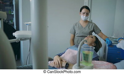 The end of dental treatment, doctor lifts up the dental...