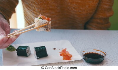 Woman Eating Sushi Roll from a Plate in a Japanese...
