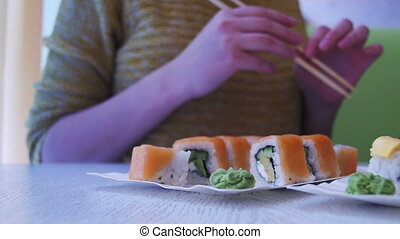 Woman with Chopsticks Takes Sushi from a Plate in a Japanese Restaurant. Dolly Shot