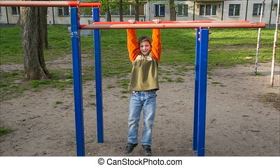 little child try pull up on the horizontal bar, outdoor