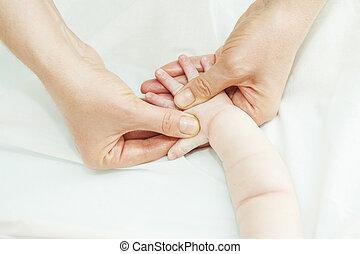 Masseur massaging a child hand