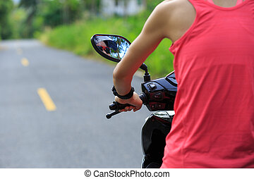 Young  woman traveling by a scooter on country road