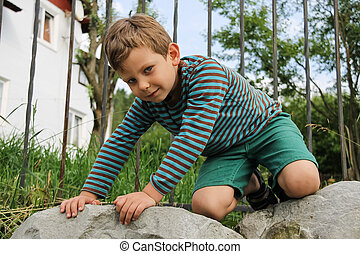 Little boy in striped sweater and shorts on big rocks