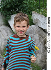 Smiling boy with dandelion in front of big rocks