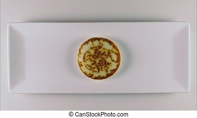 Pancakes on a white rectangular plate with topping - Three...