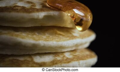 A syrup flows from the pancakes, close up on a black...