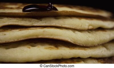 Blueberry jam flowing on pancakes on a black background....