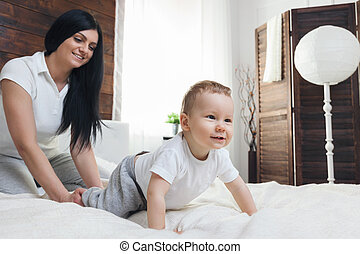 Happy mother with her cute child on the bed having a good...
