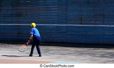 boy playing tennis practicing strokes on the wall