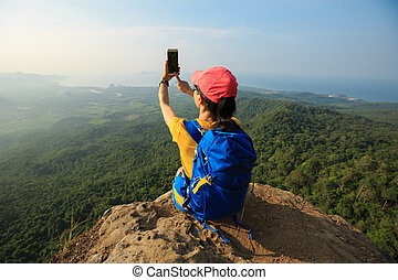 successful woman hiker taking photo with smartphone on...