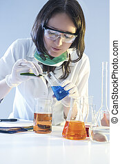 Medicine and Healthcare Concepts. Female Laboratory Staff Dealing with Flasks Filled with Chemicals Specimens During Scientific Experiment in Laboratory.