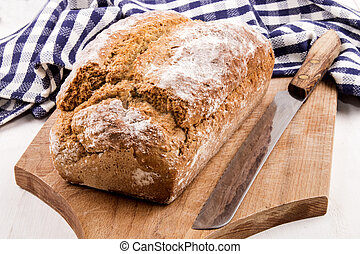 home baked irish soda bread and a bread knife on a wooden...