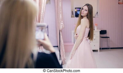 Young woman chooses a prom dress in a boutique - girl...