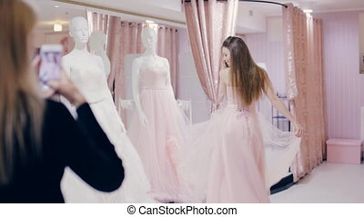 Pretty woman trying on wedding dress in fitting room - woman...