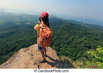 successful woman photographer on mountain peak cliff
