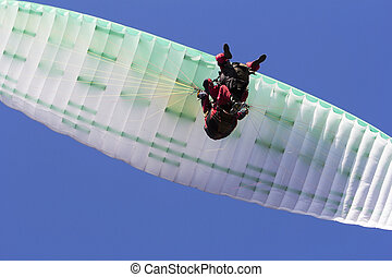 Paragliding in tandem, extreme sport, free gliding and blue sky as background