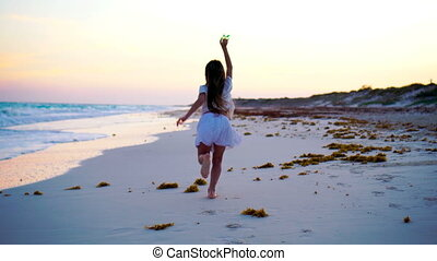 Adorable little girl with flying kite on tropical beach have a lot of fun. Kids play on ocean shore with beach toys