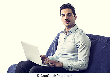 Young man working with computer on couch