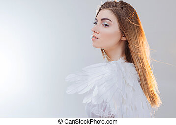 Young, wonderful blonde girl in the image of an angel with...