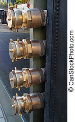 Four brass fire hose connections sticking out of a city...
