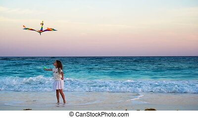 Adorable little girl with flying kite on tropical beach. Kid play on ocean shore with beautiful sunset. Slow motion.