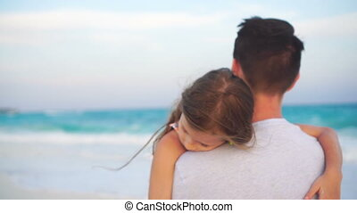 Father and his adorable little daughter at white beach. Family walking in sunset on the seashore