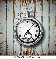 pocket watch lying on a wooden surface