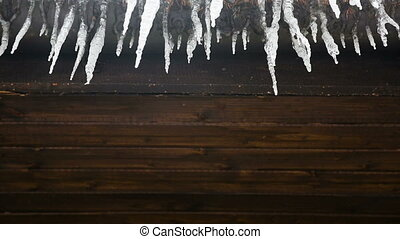 Icicles drip from a wooden roof