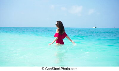 Young beautiful woman have fun in clean sea with turquoise...