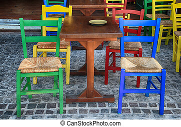 Alfresco outdoor cafe with multicolored chairs, Greece -...