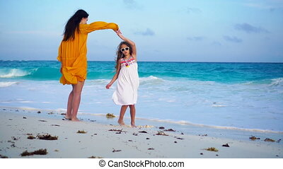 Little adorable girl and young mother at tropical beach in warm evening. Little girl dancing on the seashore at sunset