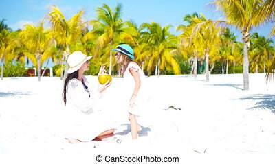 Little kid and young mom with coconut milk on exotic beach....