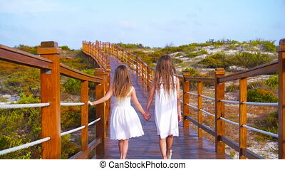 Little adorable girls on a wooden bridge on their way to a white tropical beach.