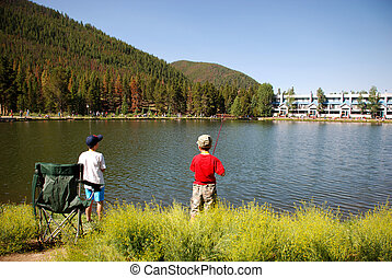 Boys fishing on lake in Colorado mountains