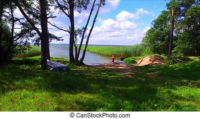 Boy playing on green grass lake shore at sunny day
