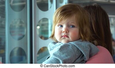 Cute baby girl looking in window